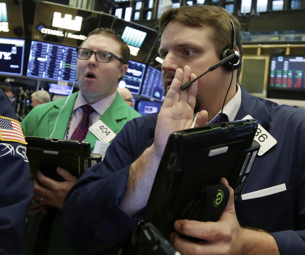 Two traders work Tuesday at the New York Stock Exchange, which has been energized by strong company earnings.