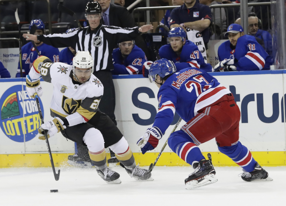 William Carrier of Vegas and Ryan McDonagh of the Rangers battle for the puck in Tuesday night's game in New York. The Rangers scored four times in the third period to win 6-4.