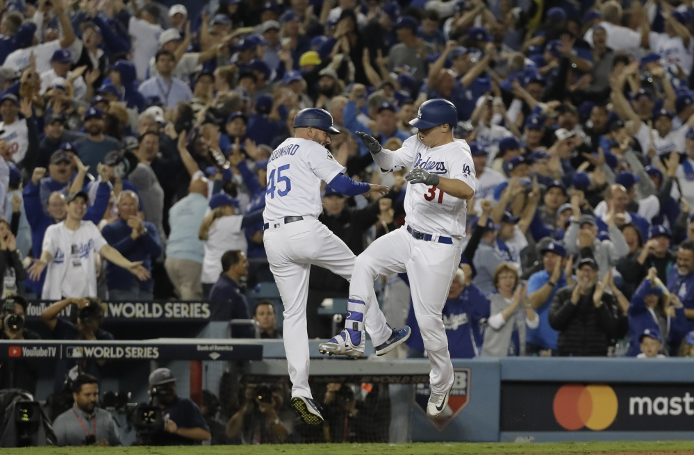Los Angeles Dodgers' Joc Pederson celebrates his seventh-inning home run with third base coach Chris Woodward. Associated Press/David J. Phillip