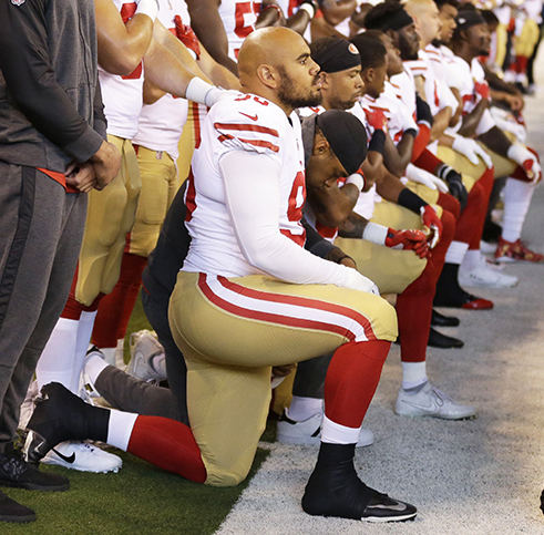 Members of the San Francisco 49ers kneel during the playing of the national anthem before an NFL football game against the Indianapolis Colts, Sunday, Oct. 8, 2017, in Indianapolis.