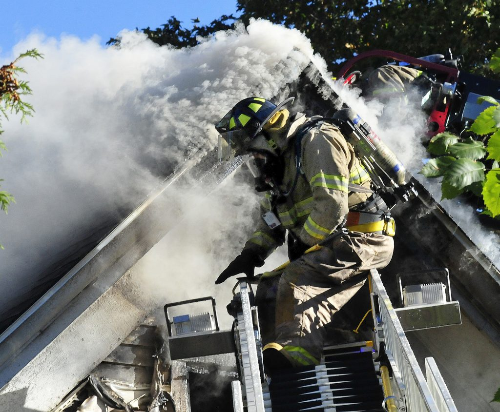 A firefighter on a ladder truck gets set up to pour water on the smokey roof of a home destroyed by fire at the corner of Main Street and Peltoma Avenue in Pittsfield on Sunday. Photo by David Leaming/Morning Sentinel