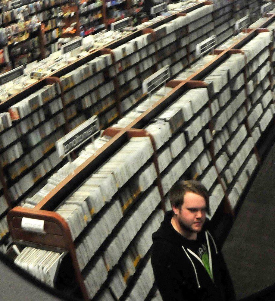 Standing next to a wall of CDs, Nick Murray speaks about the unexpected death of musician Tom Petty on Tuesday at the Bull Moose Music store in Waterville.