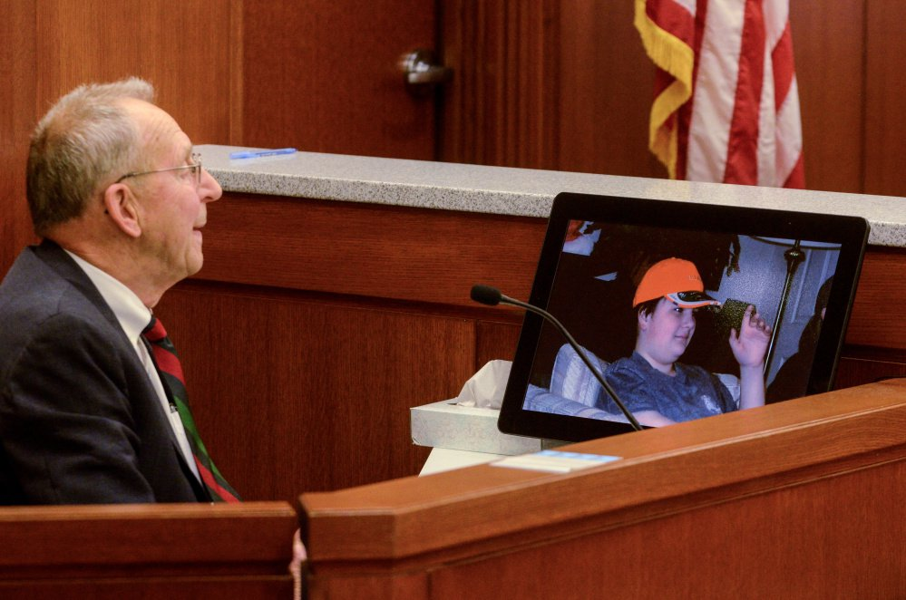 Andrew Balcer's grandfather Arthur Pierce, 82, looks at photo of Andrew during a hearing on Thursday in Augusta to determine whether Balcer should be tried as an adult for allegedly killing his parents.