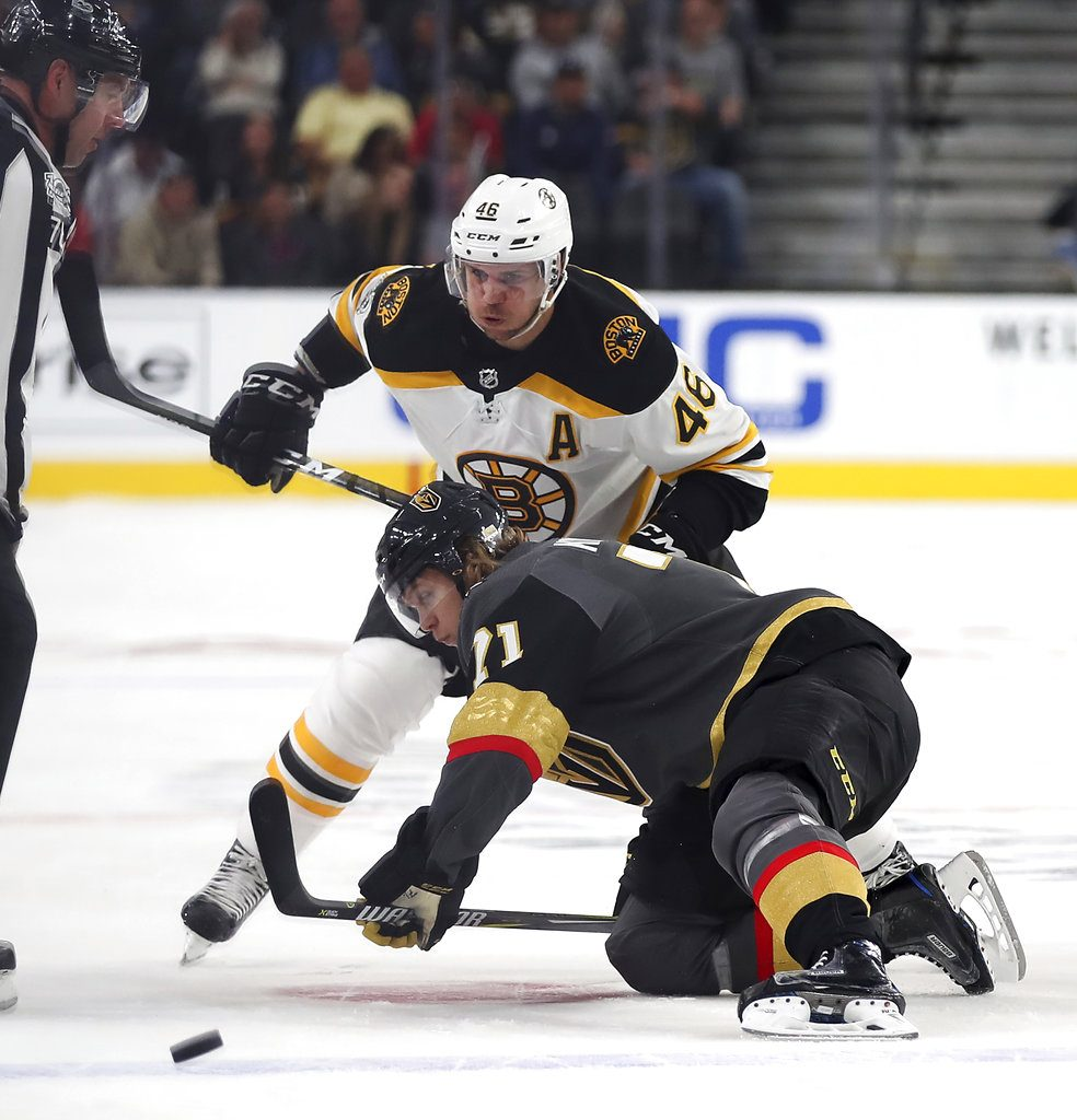 Vegas Golden Knights center William Karlsson goes to the ice to pass a puck away from Boston Bruins center David Krejci during the first period at T-Mobile Arena Sunday in Las Vegas. The Knights defeated the Bruins 3-1. (Associated Press/L.E. Baskow)