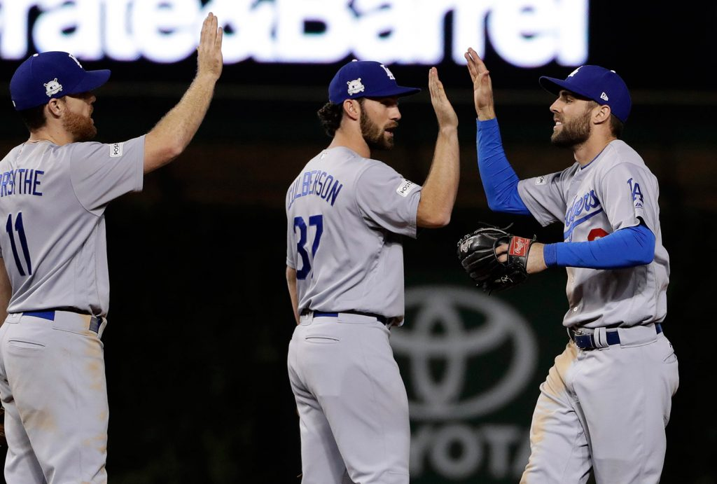 Los Angeles Dodgers' Chris Taylor, right, celebrates with Charlie Culberson (37) and Logan Forsythe (11) after Game 3 of baseball's National League Championship Series against the Chicago Cubs.