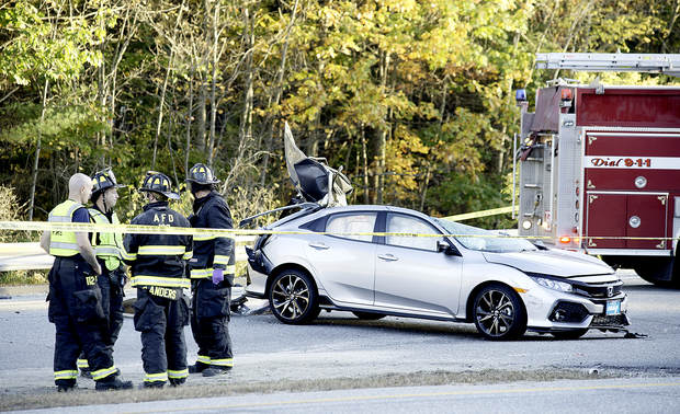 Auburn firefighters stand by after a car and tractor-trailer collided on Washington Street in Auburn on Tuesday.