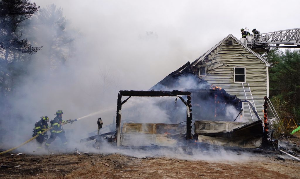 Standish firefighters battle a house fire on Middle Road in Standish on Monday. Standish Fire Chief Rob Caron says that the cause is not known yet but that responding to the fire was difficult because of roads blocked by downed trees.