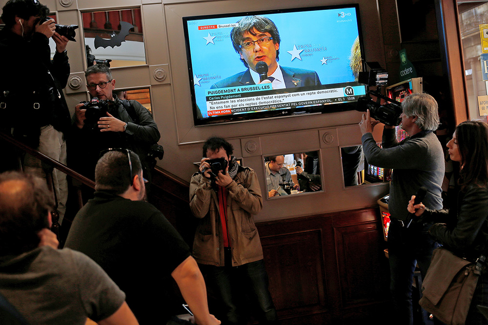 Sacked Catalan leader Carles Puigdemont is seen, during a broadcast  from Brussels, on a TV screen at a bar near  Sant Jaume square in Barcelona, Spain Tuesday.
