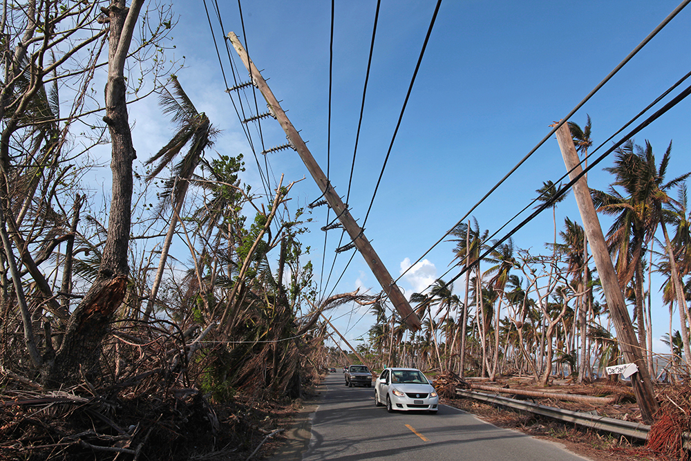 Cars drive under a partially collapsed utility pole Friday in Naguabo, Puerto Rico, amid the damage that Hurricane Maria left in September.