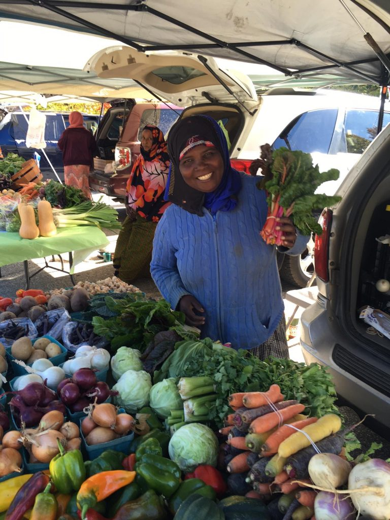 Habiba Noor offers Swiss chard from among her vegetables for sale at the Beyond Borders Farmers Market at the Viles Arboretum in Augusta. In the background is Hawa Ibrahim, who is also a farmer and a market vendor.