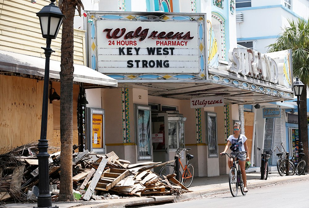 A cyclist rides past a pile of debris in Key West, Florida, recently. Irma will likely end up having caused $58 billion to $83 billion in economic losses, Moody's forecasts.