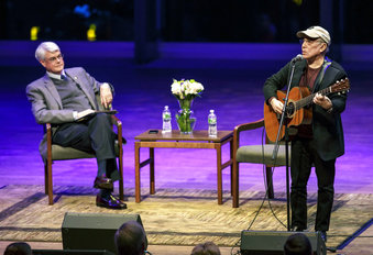 """Grammy winning recording artist Paul Simon performs a song at Skidmore College in Saratoga Springs, N.Y. The singer-songwriter visited the college to participate in a master class about songwriting, followed by an event titled """"Paul Simon: A Conversation about a Musical Life."""" At left is Skidmore President Philip A. Glotzbach."""