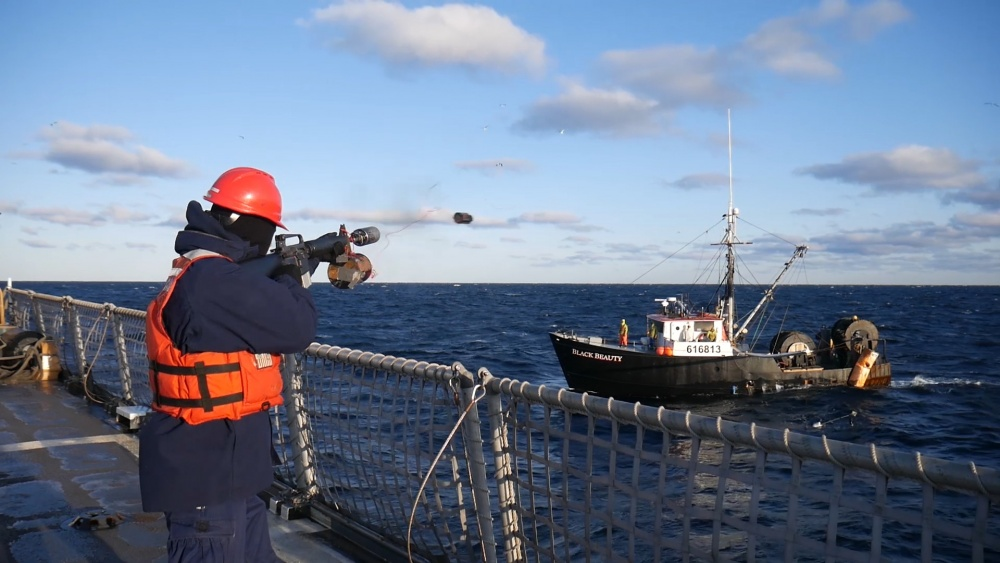 Petty Officer 3rd Class Anderson Ernst uses a line throwing gun to help pass the tow line to the 65-foot fishing troller, Black Beauty, on Saturday off the coast of New Hampshire. Coast Guard cutter Campbell, homeported in Kittery, Maine, towed the vessel to Gloucester, Massachusetts.