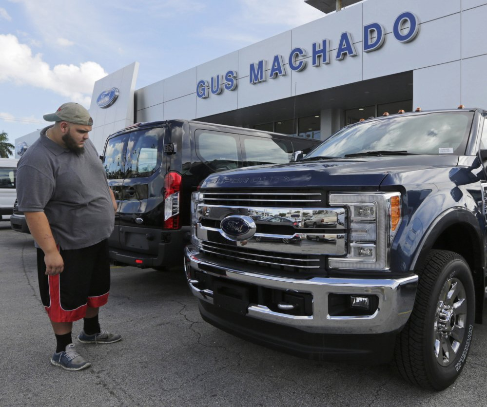 FILE - In this Tuesday, Jan. 17, 2017, file photo, a potential customer looks at a Ford F-250 Lariat FX4 at a Ford dealership, in Hialeah, Fla. Ford posted a big sales jump in October 2017 but Fiat Chrysler and General Motors reported declines as auto companies started to report numbers Wednesday, Nov. 1. The drop by two of the Detroit Three backs analysts' expectations that September's big gain in U.S. auto sales would fizzle in October. (, File)