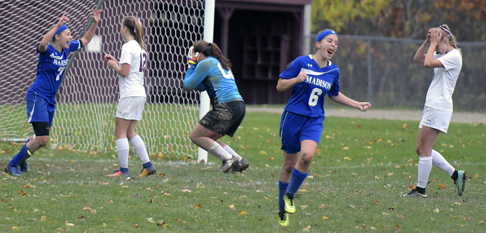 Annie Worthen, 6, and Sydney LeBlanc, left, of Madison start the celebration, and the Monmouth Academy players realize the season is over Wednesday after an overtime goal.