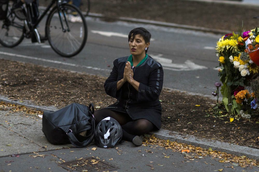 A woman sits Thursday next to a makeshift memorial for victims of Tuesday's terror attack on a bike path that left eight people dead.