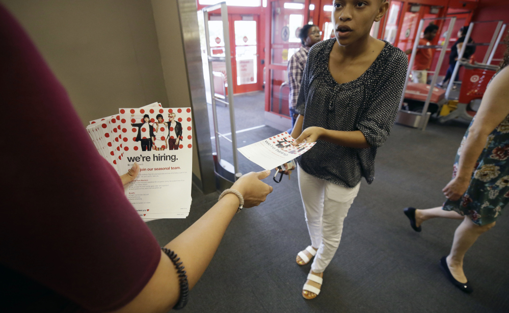 A potential job candidate takes a flyer from a human resources representative at a Target store in Dallas.