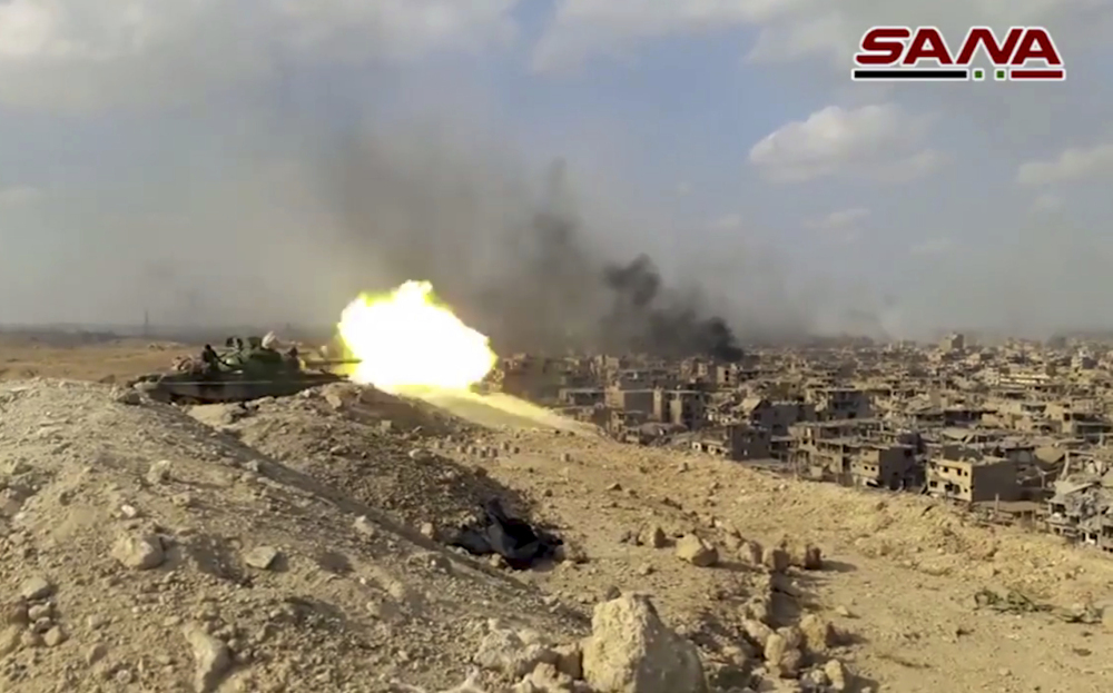 This still from a video released Thursday by the Syrian official news agency SANA shows a Syrian army tank firing during a battle against Islamic State militants in Deir el-Zour, Syria. The Syrian army announced on Friday that it liberated the long-contested eastern city from the Islamic State group.