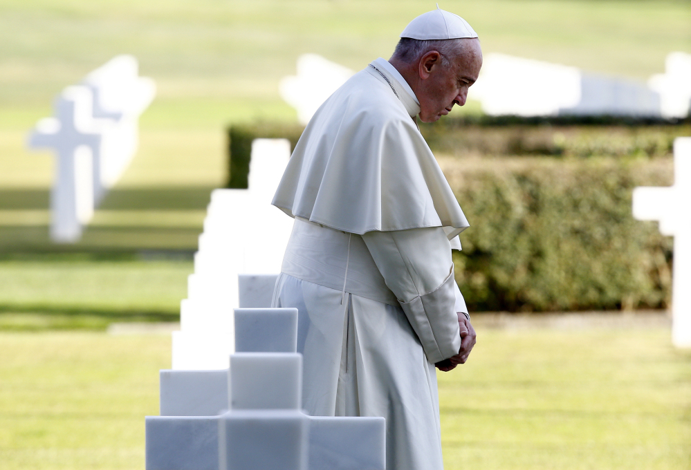 "Pope Francis walks past marble crosses at the American military cemetery in Nettuno, Italy, Thursday, later saying that the headstones should stand as a call for peace and ""no more war, no more of these useless massacres."" The pope continued to the Ardeatine Caves, site of one of the worst massacres of Nazi-occupied Rome. Francis became the fourth pope to visit the caves, after Paul VI, John Paul II and Benedict XVI."