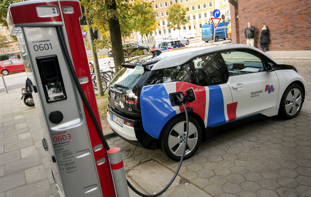 An electric vehicle is connected to a charging station in Hamburg, Germany, last month. Major automakers say their joint European electric-car recharging network will provide a big step toward mass acceptance of battery-powered cars.
