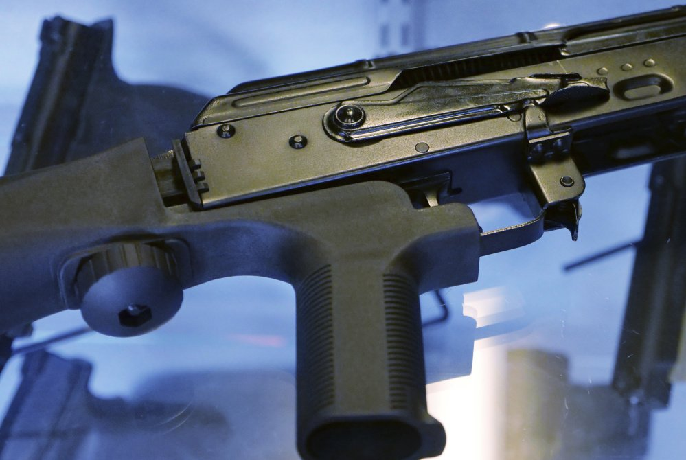 A bump stock is shown attached to a semi-automatic rifle.