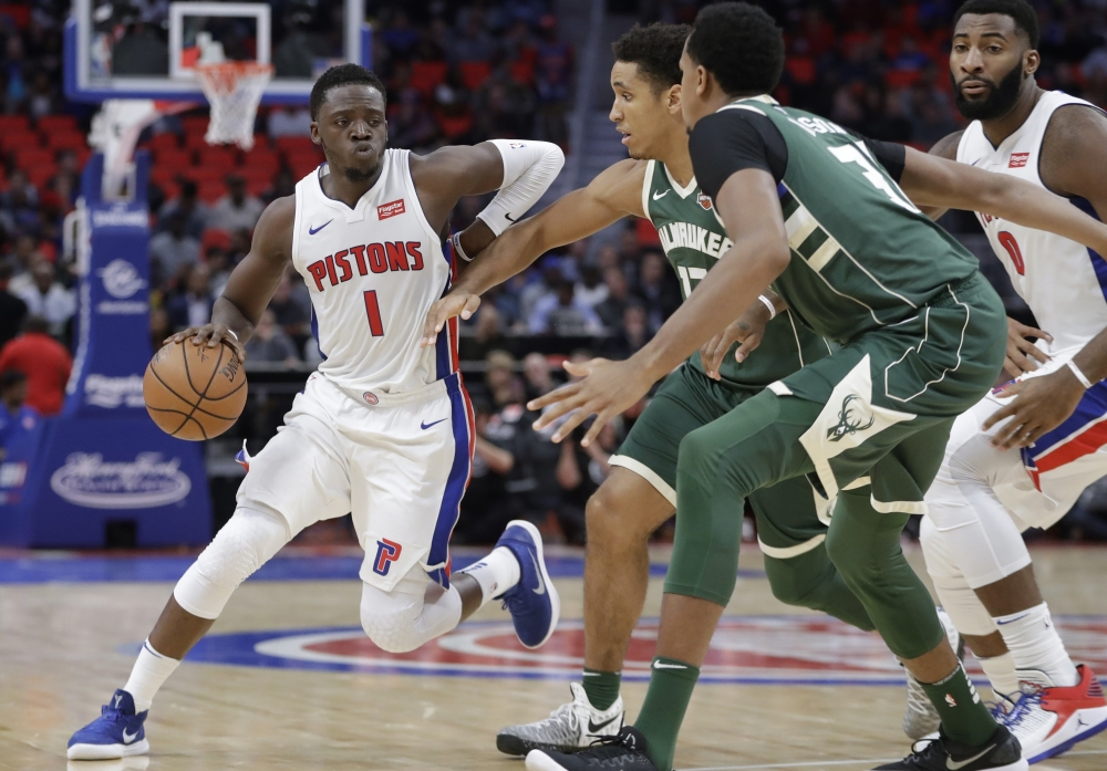 Reggie Jackson of the Detroit Pistons looks for room as Malcolm Brogdon, center, and John Henson of the Milwaukee Bucks move in to defend Friday night during the first period of the Pistons' 105-96 victory at home.