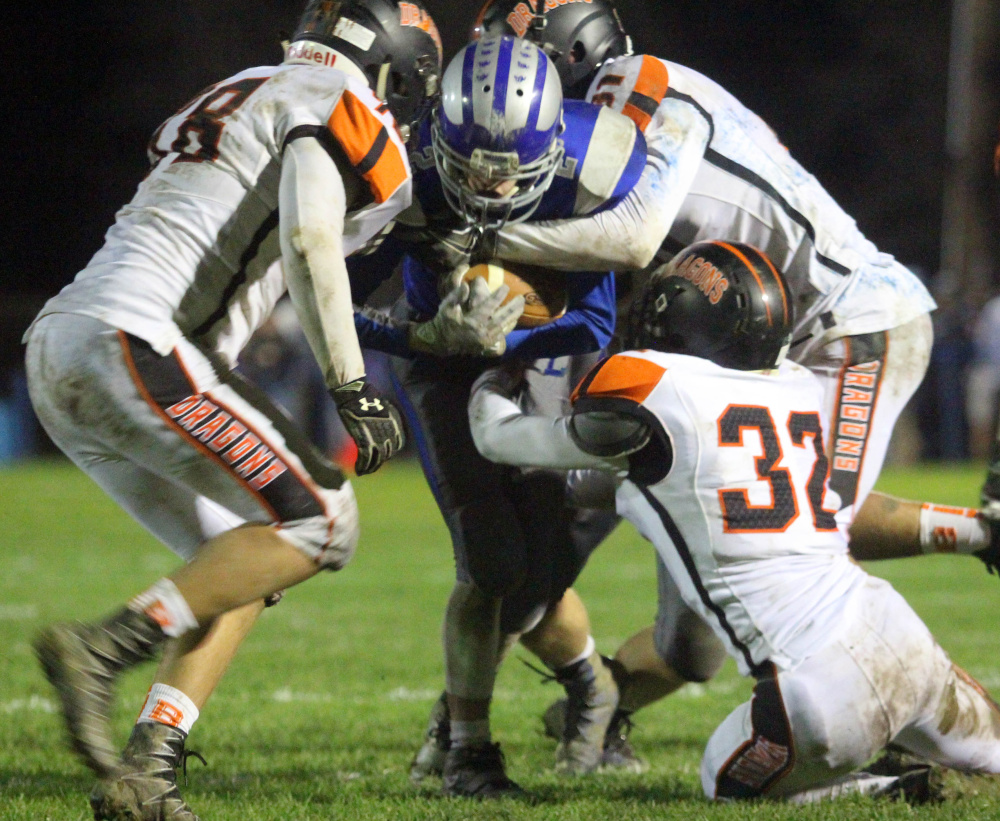 Lawrence running back Isaiah Schooler is brought down by Brunswick's Bailey Pelletier, left, Sam Dorval, back, and Jack Harvey.