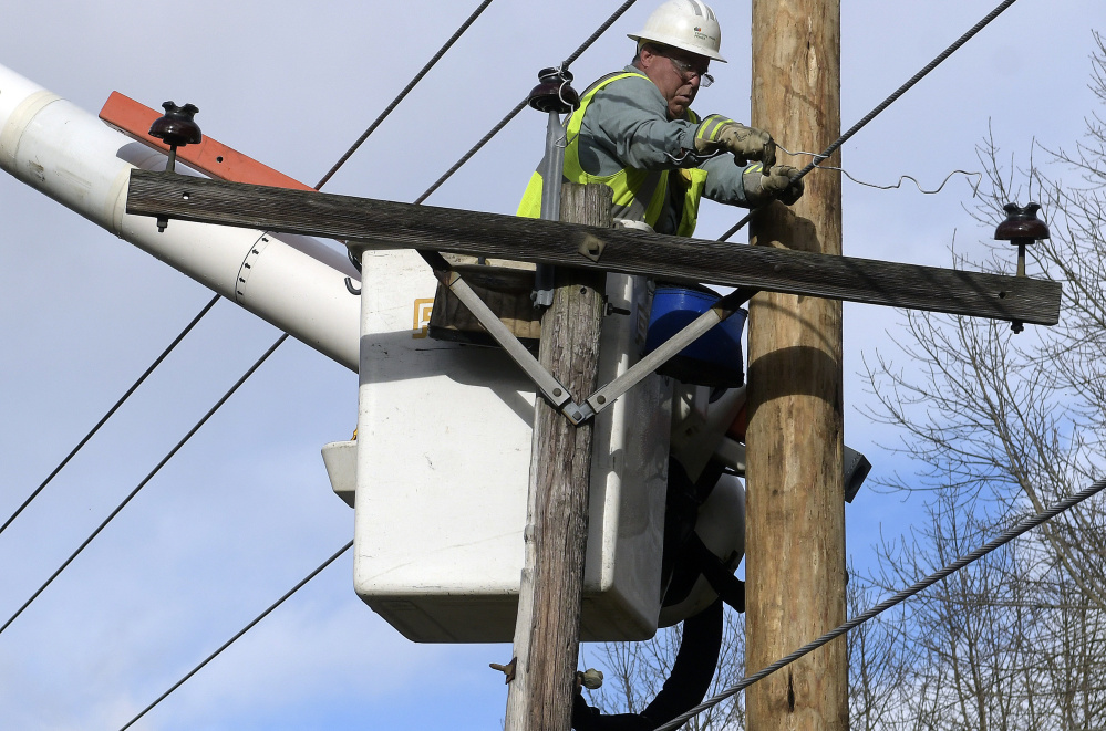 Central Maine Power Co. lineman Wayne Piper unhooks a pole Monday after it snapped on South Monmouth Road in Monmouth. Response to storm damage has earned praise, owing in part to lessons learned from the Ice Storm of 1998.