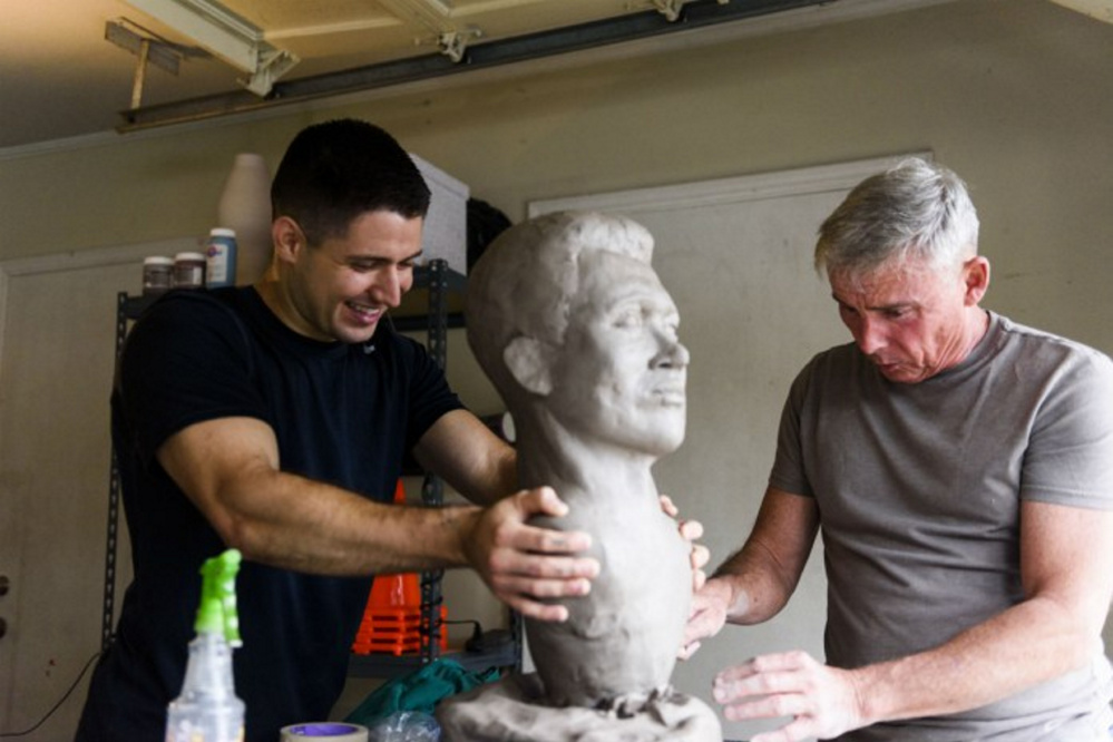 "Steven Arango holds the bust of Bates College graduate George ""Alexi"" Whitney, while artist and retired Marine Col. Lee Busby of Alabama works on the details."