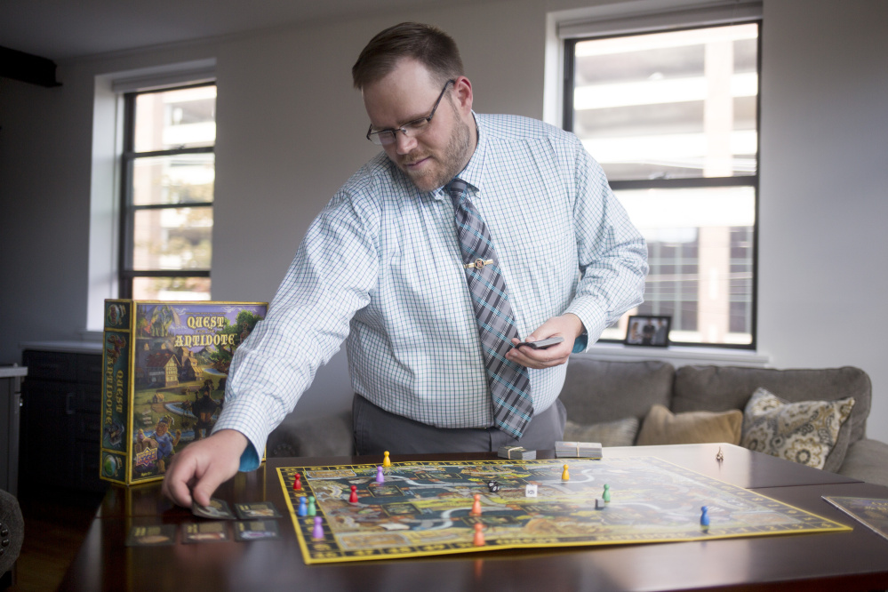 Tom Deschenes sets up the board game he invented, Quest for the Antidote, at his apartment in Portland. It took him five years to create and design the game.