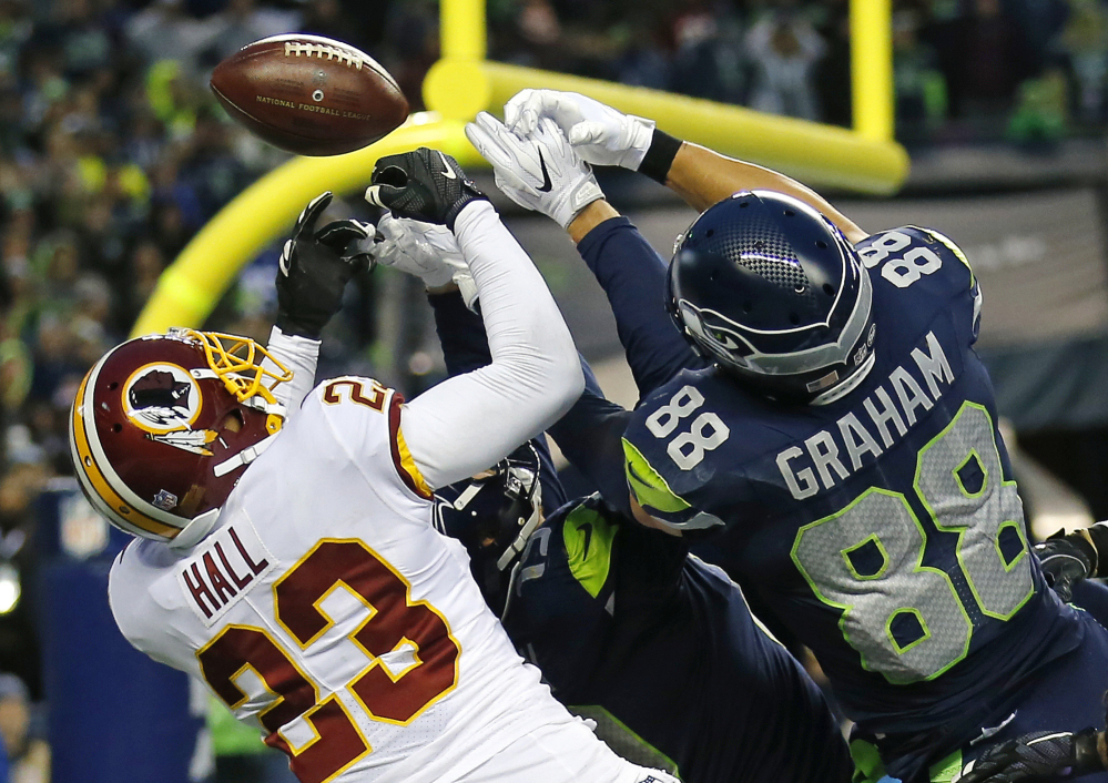 Washington safety DeAngelo Hall breaks up a Hail Mary pass against Jimmy Graham, right, and Tanner McEvoy of the Seahawks on the final play of a 17-14 win Sunday in Seattle.