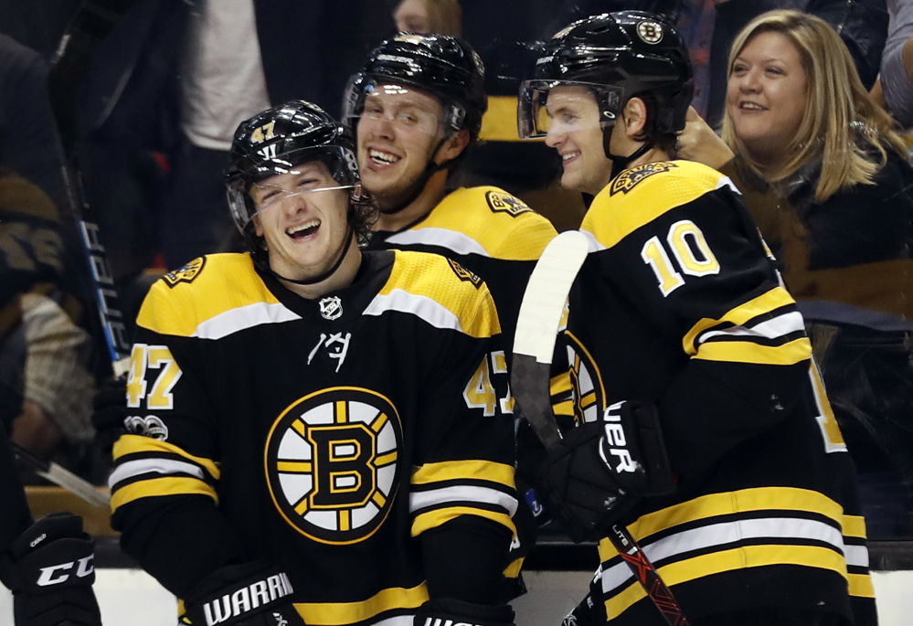 Boston Bruins' Torey Krug (47) laughs with David Pastrnak and Anders Bjork (10) after his goal in the second period.
