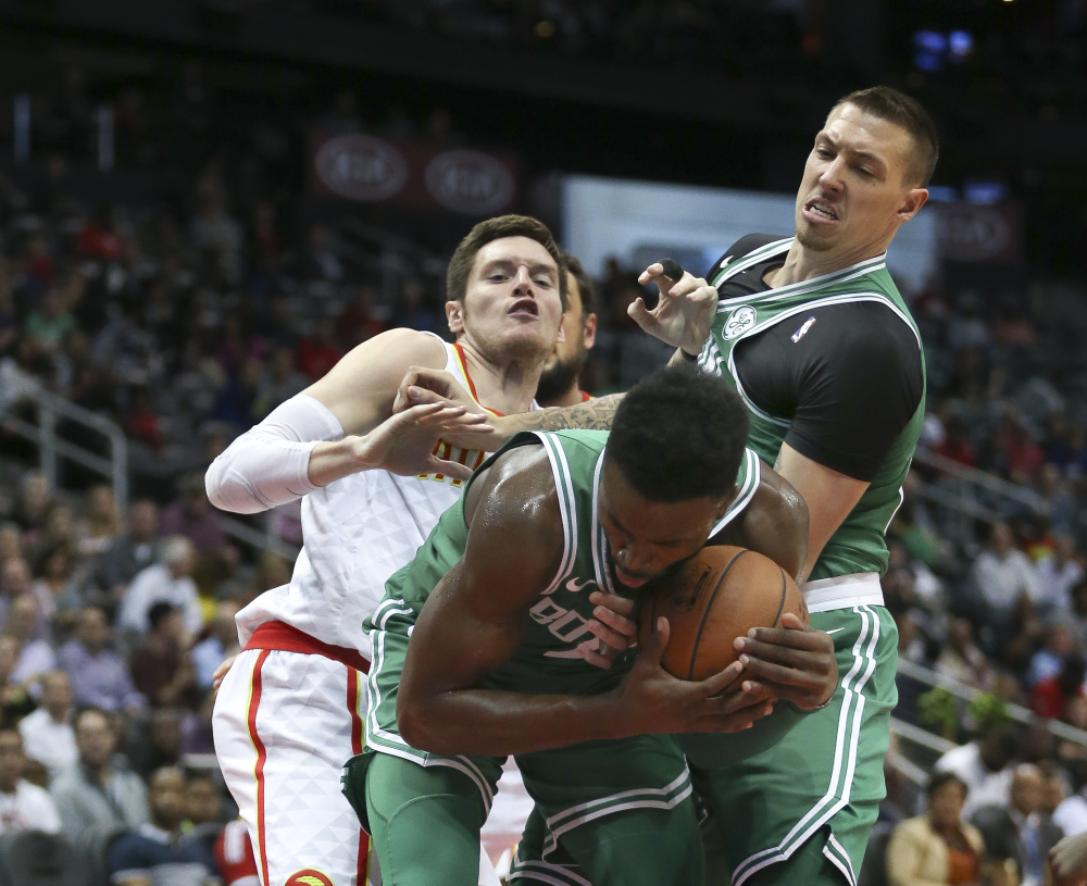 Celtics guard Jaylen Brown grabs a rebound as Atlanta forward Luke Babbitt and Boston forward Daniel Theis also battle for the ball.