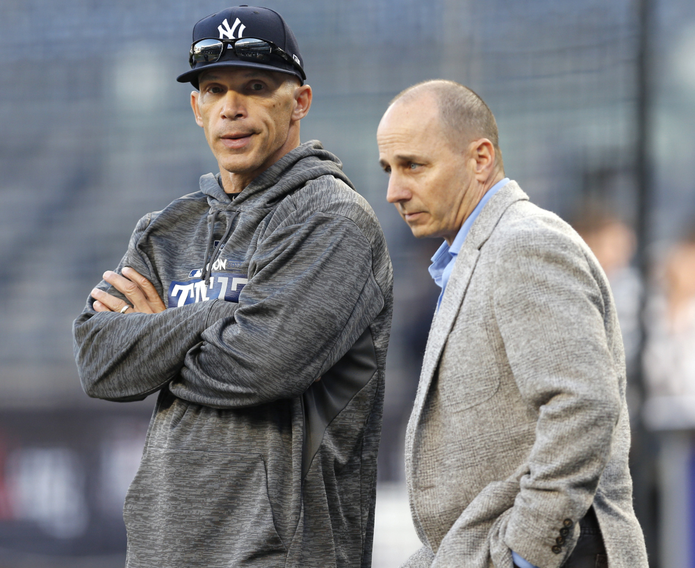 Yankees General Manager Brian Cashman, right, said former manager Joe Girardi, left, may have faced hurdles communicating with his players after 10 years on the job.