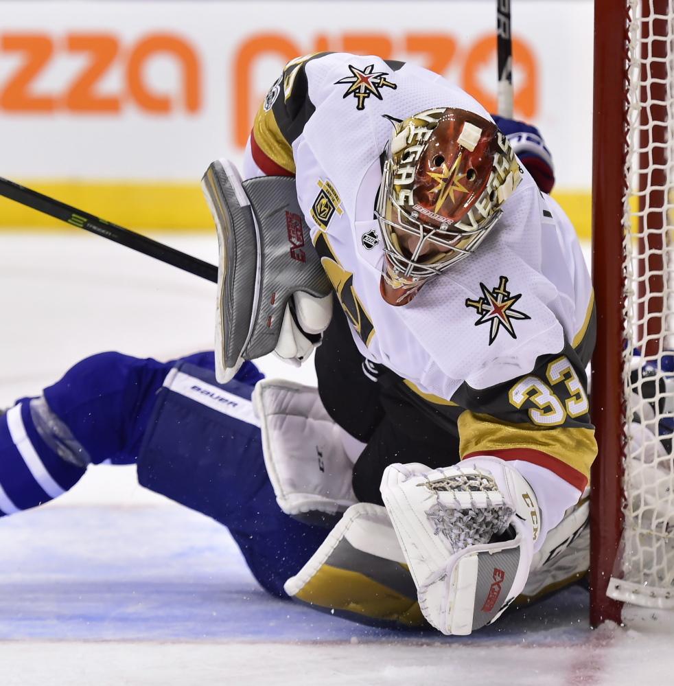 Vegas Golden Knights goalie Maxime Lagace is run over by Maple Leafs forward Zach Hyman, obscured, during the second period of Toronto's 4-3 shootout win at home Monday.