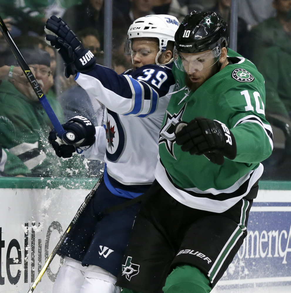 Winnipeg defenseman Toby Enstrom and Dallas center Martin Hanzal slam against the boards chasing a loose puck in the first period Monday night in Dallas.
