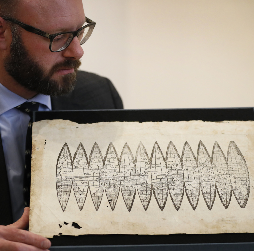 "Cartographer Martin Waldseemueller displays a 510-year-old map dubbed ""America's birth certificate"" at Christie's auction rooms in London on Tuesday."