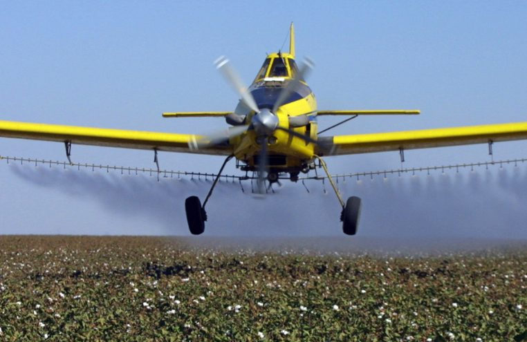 A plane dusts cotton crops in Lemoore, Calif. A new rule announced Tuesday makes spraying certain pesticides within a quarter mile of a school a fine-able offense.