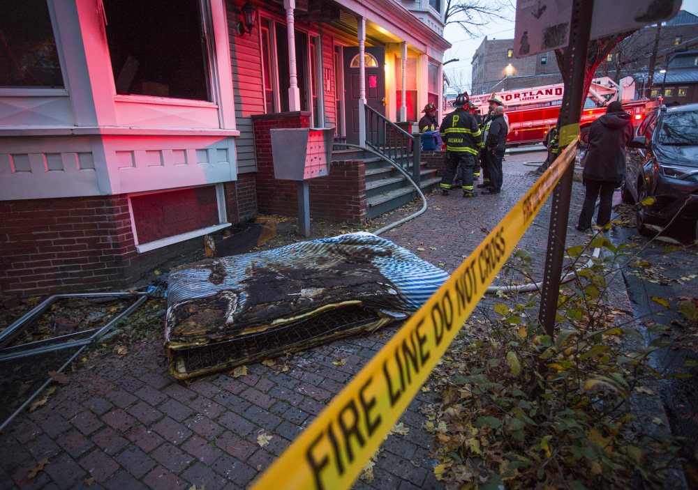 Investigators work Tuesday at 3 Sherman St. in Portland after a fire displaced 13 tenants. One tenant, Peter Sullivan, said he climbed out of his bedroom window to get to safety.