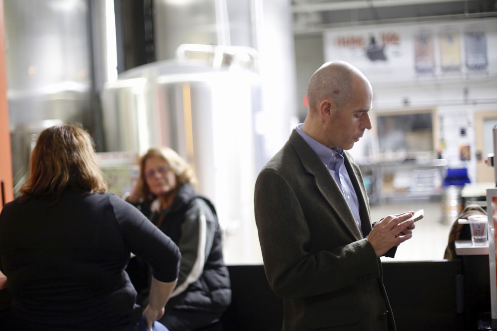 Brit Vitalius, spokesman for Say No to Rent Control, checks his phone while attending an election results gathering Tuesday at Rising Tide Brewing Co. in Portland.