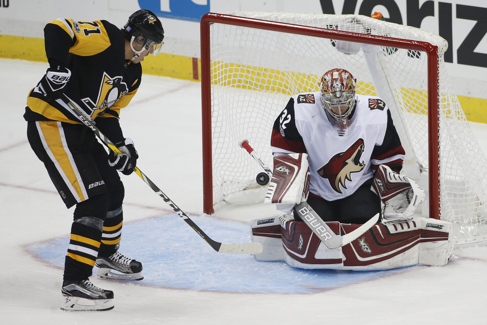 Pittsburgh's Evgeni Malkin deflects a rebound past Arizona goalie Antti Raanta in the first period Tuesday night in Pittsburgh. Malkin also added two assists as the Penguins won 3-1.
