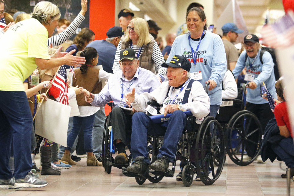 Fanfare greets Maine veterans at the Portland Jetport as they return from an Honor Flight to Washington, D.C.