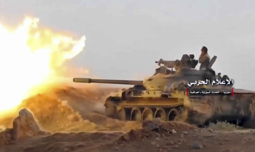 The frame from a video by the government-controlled Syrian Central Military Media shows a tank firing on militants' positions on the Iraq-Syria border.