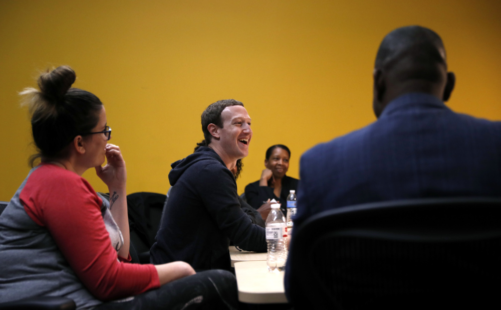 Facebook CEO Mark Zuckerberg, center, meets entrepreneurs and innovators at Cortex Innovation Community hub Thursday in St. Louis. Zuckerberg announced a program to boost small businesses and bolster digital skills.