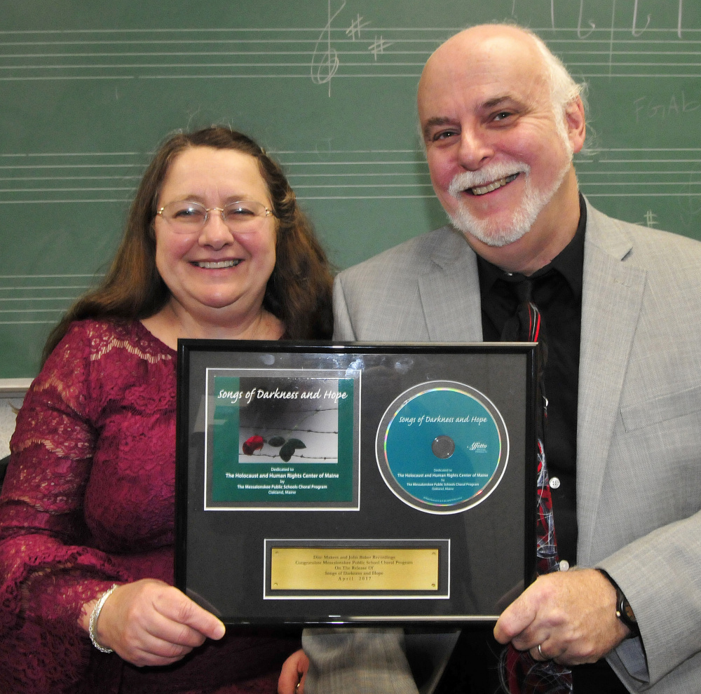 "Messalonskee High School Concert Chorus co-directors Pam and Kevin Rhein show copies Thursday of ""Songs of Darkness and Hope,"" performed by Messalonskee students, which is nominated for a Grammy Award in the choral category."