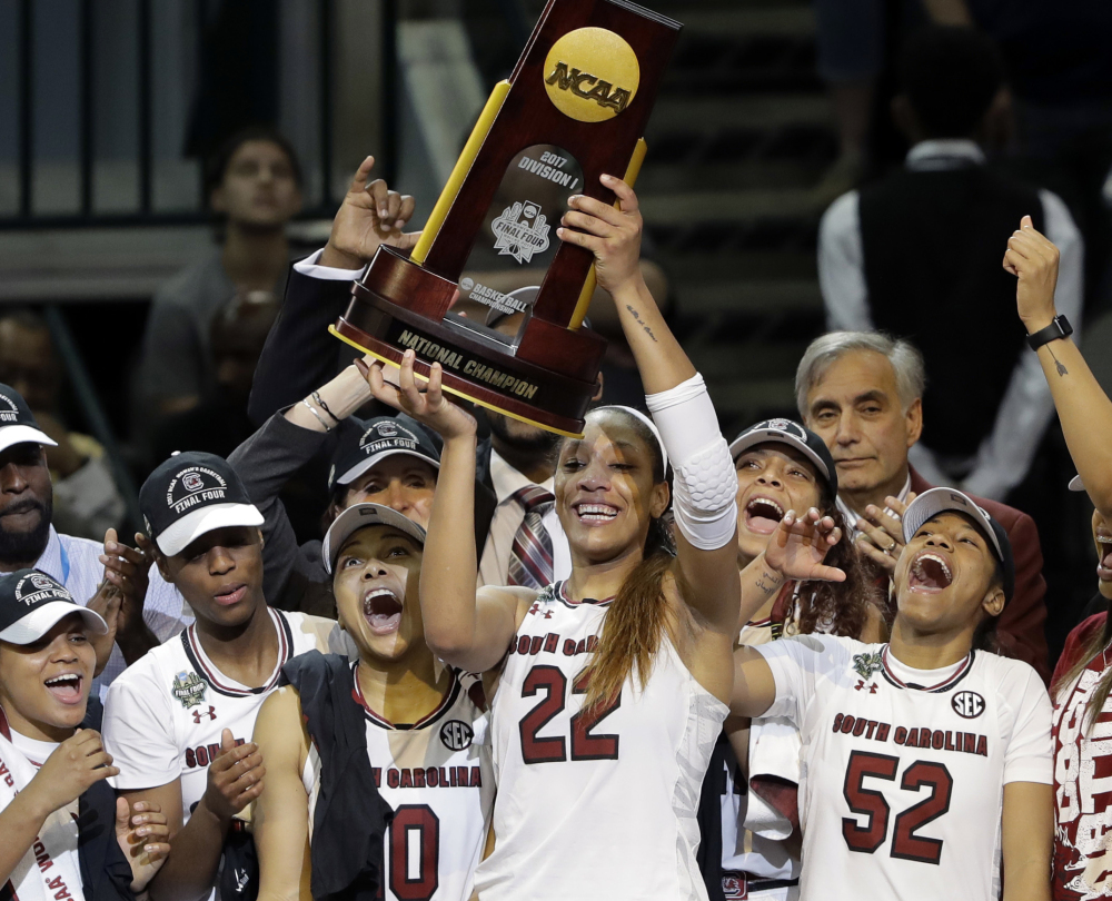 A'ja Wilson, holding last year's NCAA championship trophy, is one of only two returning starters for South Carolina, but the Gamecocks are expected to be strong again.