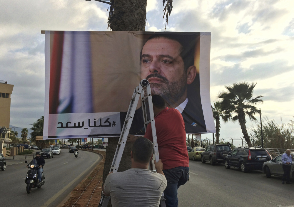 Workers hang a poster of outgoing Prime Minister Saad Hariri with Arabic words that read,