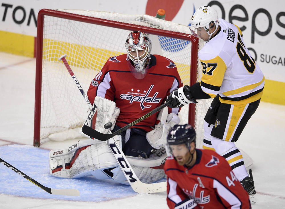Penguins center Sidney Crosby battles for the puck against Washington goalie Braden Holtby in the third period Friday night in Washington. Holtby became the second-fastest goaltender in NHL history behind Ken Dryden to reach 200 victories with a 4-1 win.