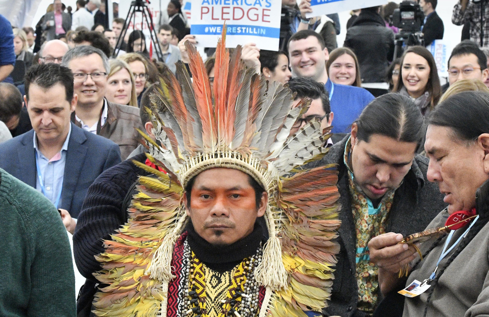 """Native Americans wait in the U.S. Climate Action Center for the """"America's Pledge"""" and """"We Are Still In"""" campaign in Bonn, Germany, on Saturday."""