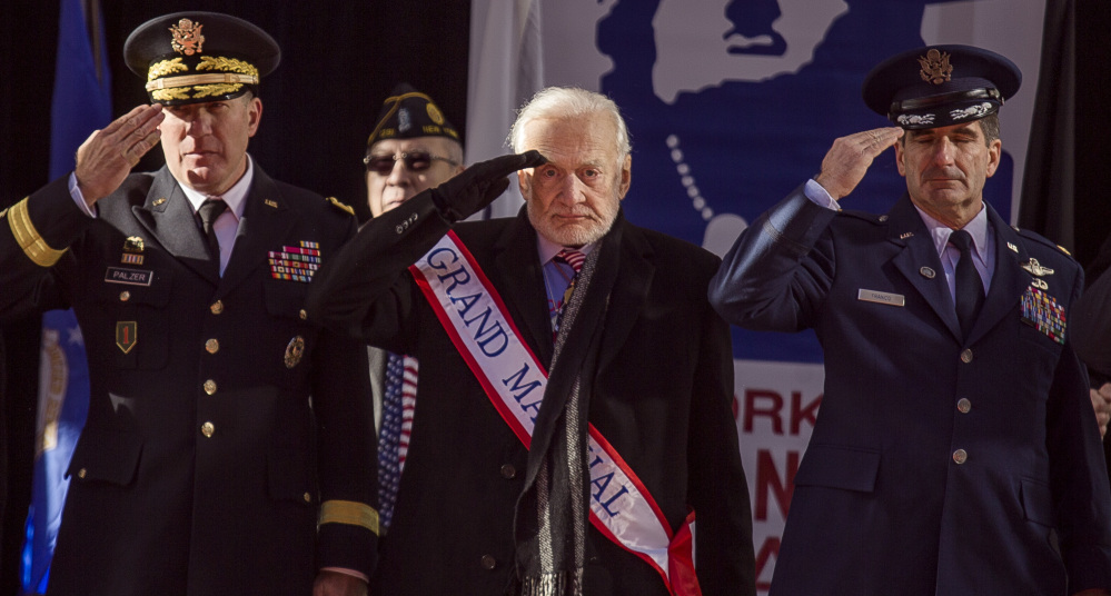 Former astronaut Buzz Aldrin, center, salutes during the annual Veterans Day parade in New York on Saturday. Aldrin served as grand marshal as he joined Mayor Bill de Blasio.